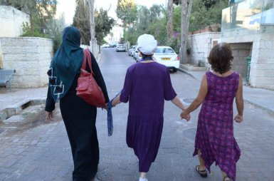 Three women hold hands during the interfaith peace walk between the eastern and western parts of Jerusalem on Sept. 21, 2015 after an interfaith group gathering between Jews and Muslims. Photo courtesy of The Abrahamic Reunion
